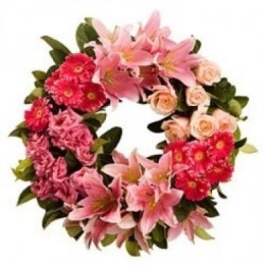 Corona rosada de rosas, gerberas y lirios en tonos rosados