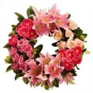 Corona blanca de rosas, gerberas y lirios en tonos rosados